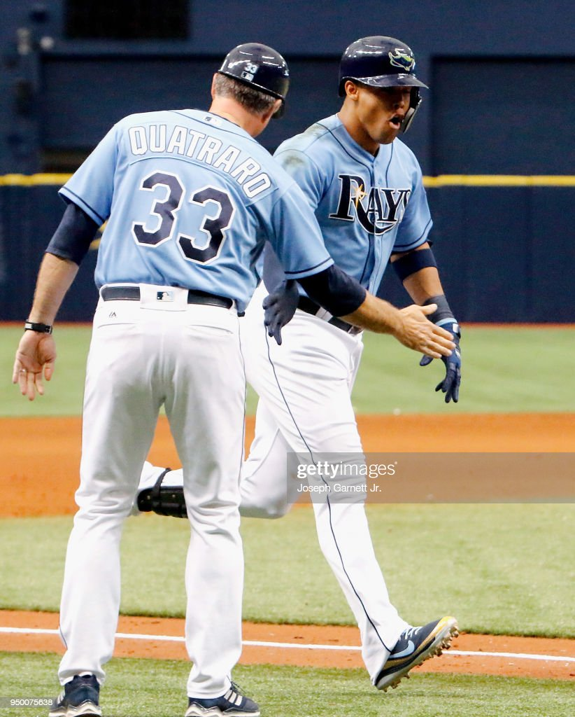 Matt Quatraro #33 of the Tampa Bay Rays congratulates Carlos Gomez #27 at third base after he hit a game-winning two-run home run against the Minnesota Twins in the ninth inning at Tropicana Field on April 22, 2018 in St. Petersburg, Florida.