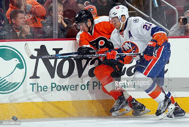 Matt Read of the Philadelphia Flyers battles along the boards for the loose puck with Kyle Okposo of the New York Islanders on December 8 2015 at the...