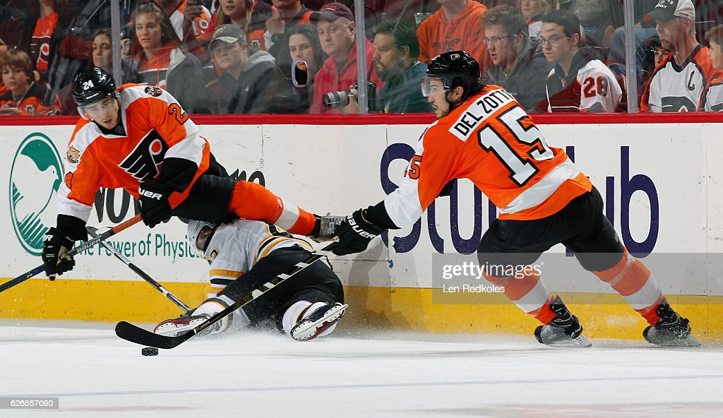 Matt Read #24 of the Philadelphia Flyers collides along the boards with Torey Krug #47 of the Boston Bruins as Flyer Michael Del Zotto #15 controls the puck on November 29, 2016 at the Wells Fargo Center in Philadelphia, Pennsylvania. The Flyers went on to defeat the Bruins 3-2 in a shootout.