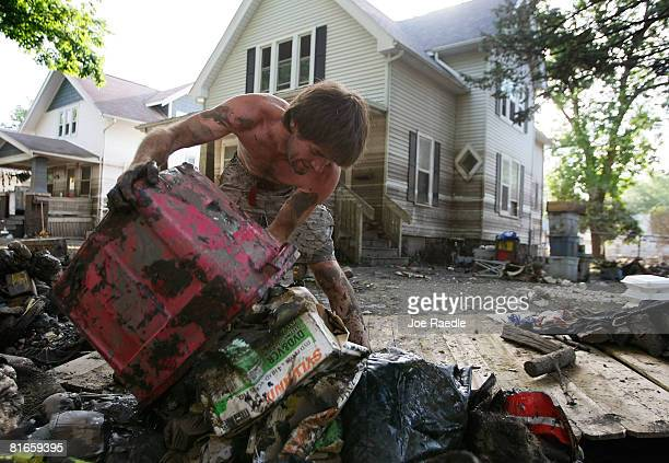 Matt Regan dumps debris from his home that was ruined by the flood water of the Iowa River onto the curb as he cleans out the house June 21, 2008 in...