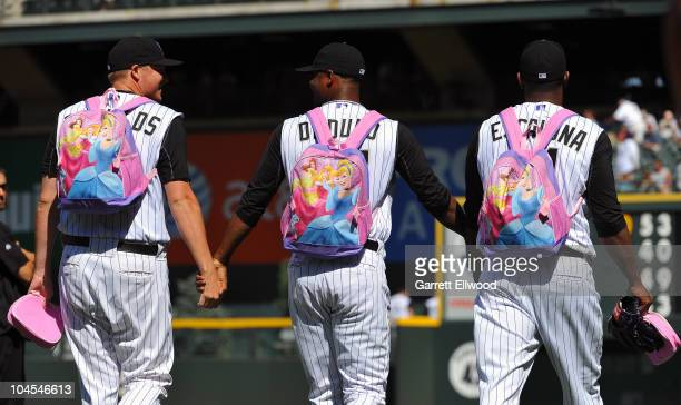 Matt Reynolds Samuel Deduno and Edgmer Escalona of the Colorado Rockies hold hands as they walk to the bullpen while wearing princess themed...