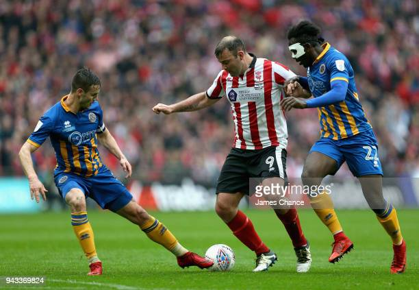 Matt Rhead of Lincoln City is challenged by Aristote Nsiala of Shrewsbury Town and Mat Sadler of Shrewsbury Town during the Checkatrade Trophy Final...