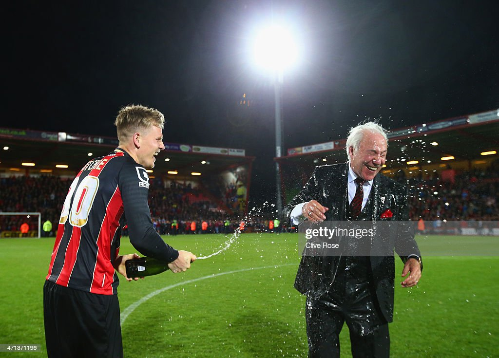 Matt Ritchie of Bournemouth sprays Bournemouth chairman Jeff Mostyn with champagne as they celebrate victory on the pitch after the Sky Bet Championship match between AFC Bournemouth and Bolton Wanderers at Goldsands Stadium on April 27, 2015 in Bournemouth, England. Bournemouth's 3-0 victory puts them on the brink of promotion to the Barclays Premier League.