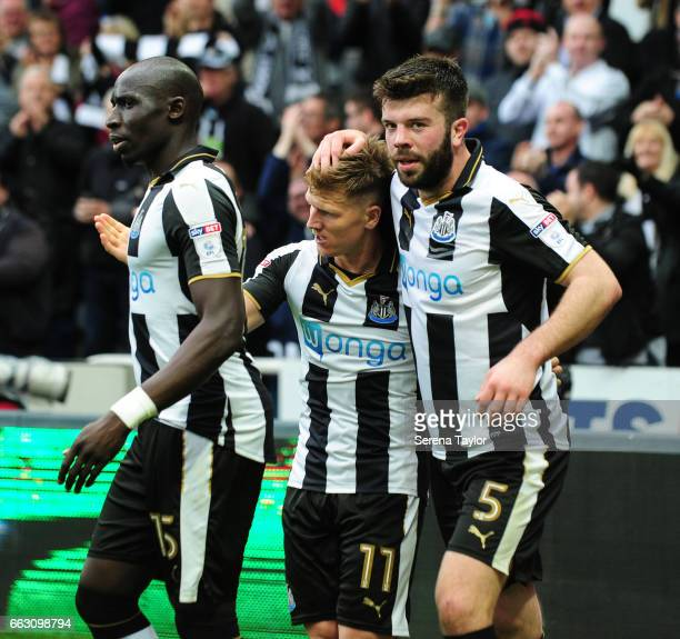 Matt Ritchie of Newcastle United celebrates with teammates Mohamed Diame and Grant Hanley after scoring Newcastle's second goal during the Sky Bet...