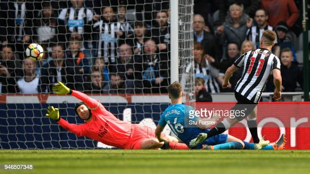 Matt Ritchie of Newcastle United scores his sides second goal past Petr Cech of Arsenal while being challenged by Rob Holding of Arsenal during the...