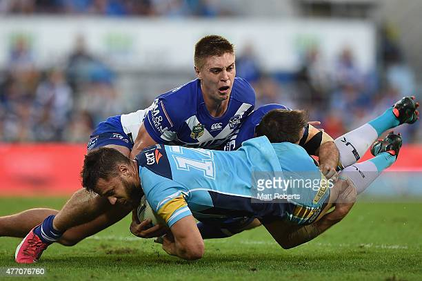 Matt Robinson of the Titans is tackled during the round 14 NRL match between the Gold Coast Titans and the Canterbury Bulldogs at Cbus Super Stadium...