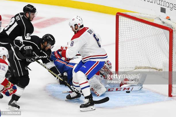 Matt Roy and Alex Iafallo of the Los Angeles Kings apply pressure against Jordie Benn of the Montreal Canadiens as goaltender Carey Price of the...