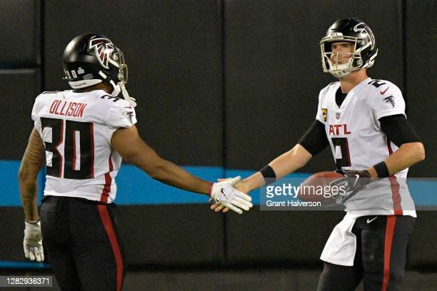 Matt Ryan celebrates a touchdown run with teammate Qadree Ollison of the Atlanta Falcons against the Carolina Panthers during the second quarter at...