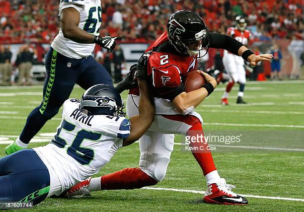 Matt Ryan of the Atlanta Falcons draws a horsecollar penalty from Cliff Avril of the Seattle Seahawks at Georgia Dome on November 10 2013 in Atlanta...