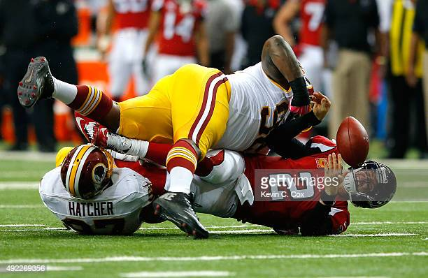 Matt Ryan of the Atlanta Falcons fumbles the ball as he is tackled by Jason Hatcher and Chris Baker of the Washington Redskins at Georgia Dome on...