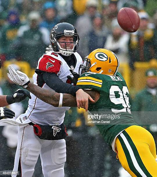 Matt Ryan of the Atlanta Falcons is hit while passing by Mike Neal of the Green Bay Packers at Lambeau Field on December 8, 2013 in Green Bay,...