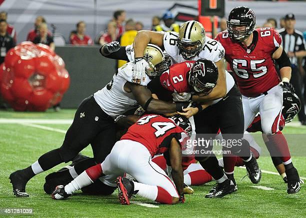 Matt Ryan of the Atlanta Falcons is sacked by Keyunta Dawson and Akiem Hicks of the New Orleans Saints at the Georgia Dome on November 21 2013 in...
