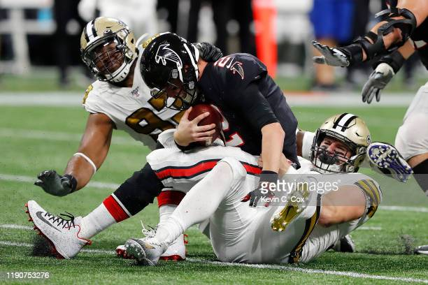 Matt Ryan of the Atlanta Falcons is sacked by Trey Hendrickson and David Onyemata of the New Orleans Saints during the second quarter at MercedesBenz...