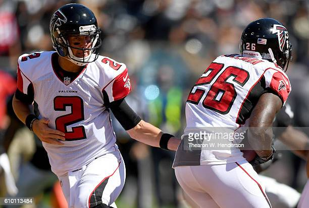Matt Ryan of the Atlanta Falcons turns to hand the ball off to running back Tevin Coleman against the Oakland Raiders in the first haft of their NFL...