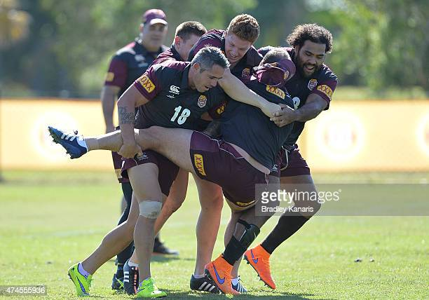 Matt Scott is tackled by Sam Thaiday and Corey Parker during the Queensland Maroons State of Origin training session at Sanctuary Cove on May 24 2015...