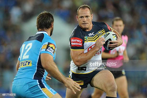 Matt Scott of the Cowboys is takes on the defence during the round four NRL match between the Gold Coast Titans and North Queensland Cowboys at Cbus...