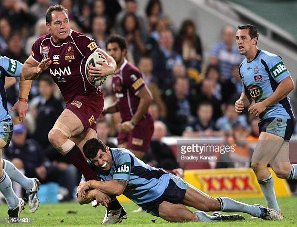 Matt Scott of the Maroons breaks through the Blues defence during game one of the ARL State of Origin series between the Queensland Maroons and the...