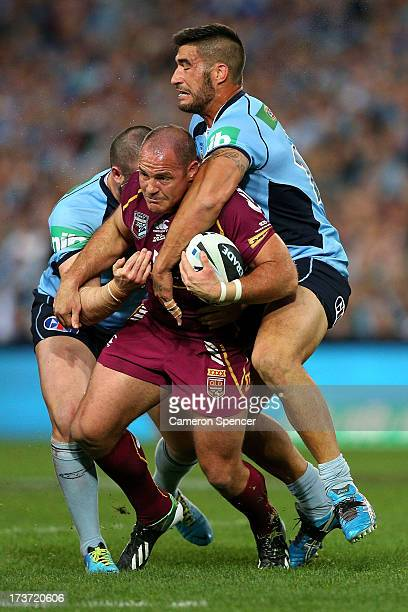 Matt Scott of the Maroons is tackled during game three of the ARL State of Origin series between the New South Wales Blues and the Queensland Maroons...