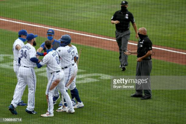 Matt Shoemaker of the Toronto Blue Jays is held back by teammates after umpire Vic Carapazza ejected him from the game during the fourth inning of...