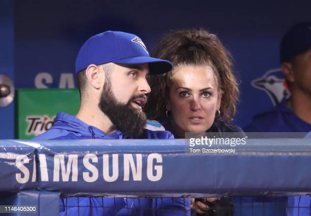 Matt Shoemaker of the Toronto Blue Jays talks to head athletic trainer Nikki Huffman as they watch from the dugout during MLB game action against the...