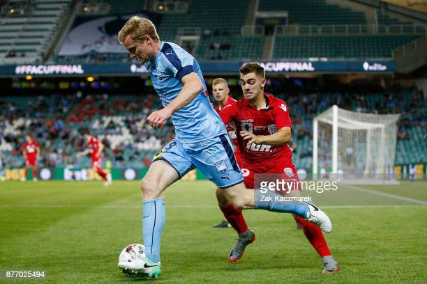 Matt Simon of Sydney evades a challenge by Ben Garuccio of Adelaide during the FFA Cup Final match between Sydney FC and Adelaide United at Allianz...