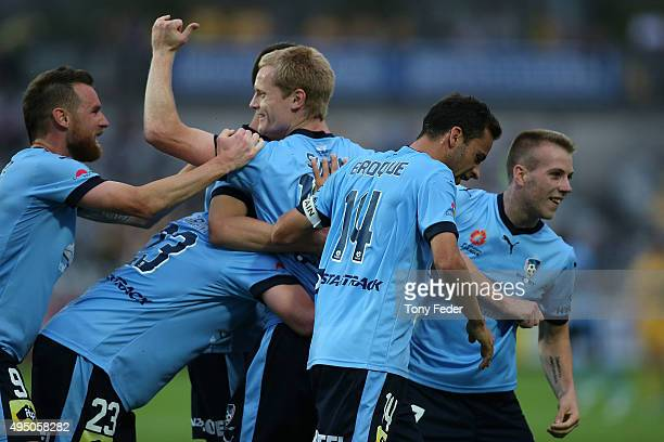 Matt Simon of Sydney FC celebrates with team mates after scoring a goal during the round four ALeague match between the Central Coast Mariners and...