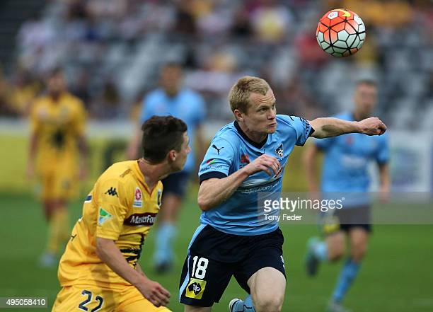 Matt Simon of Sydney FC contests a header with Jake McGing of the Mariners during the round four A-League match between the Central Coast Mariners...