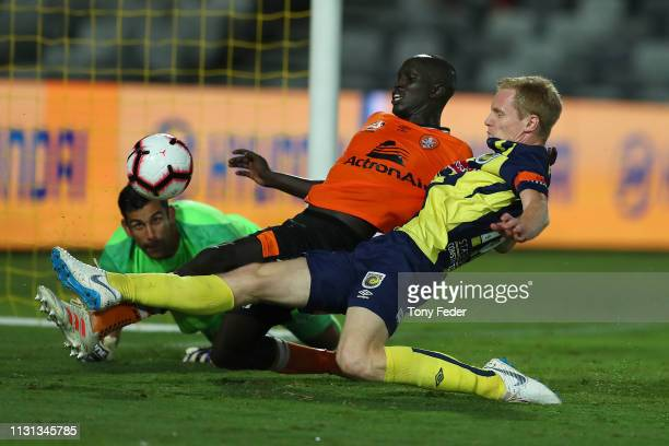 Matt Simon of the Central Coast Mariners contests the ball with Ruon Tongyik of Brisbane Roar during the Round 20 A-League Match between the Central...