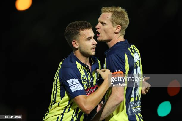 Matt Simon of the Central Coast Mariners is restrained by team mate Jordan Murray after getting sent off during the Round 20 A-League Match between...