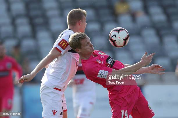 Matt Simon of the Mariners and Jordan Elsey of Adelaide contest the ball during the round three A-League match between the Central Coast Mariners and...