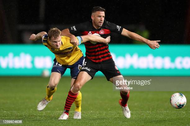 Matt Simon of the Mariners and Matthew Jurman of the Wanderers compete for the ball during the round 28 A-League match between the Central Coast...