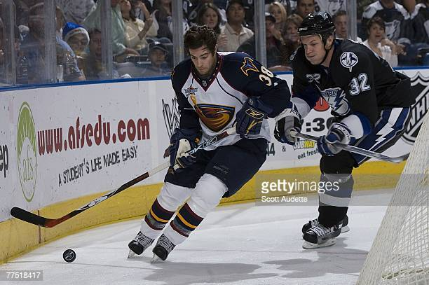 Matt Smaby of the Tampa Bay Lightning and Darren Haydar of the Atlanta Thrashers chases down the puck along the boards at St. Pete Times Forum on...