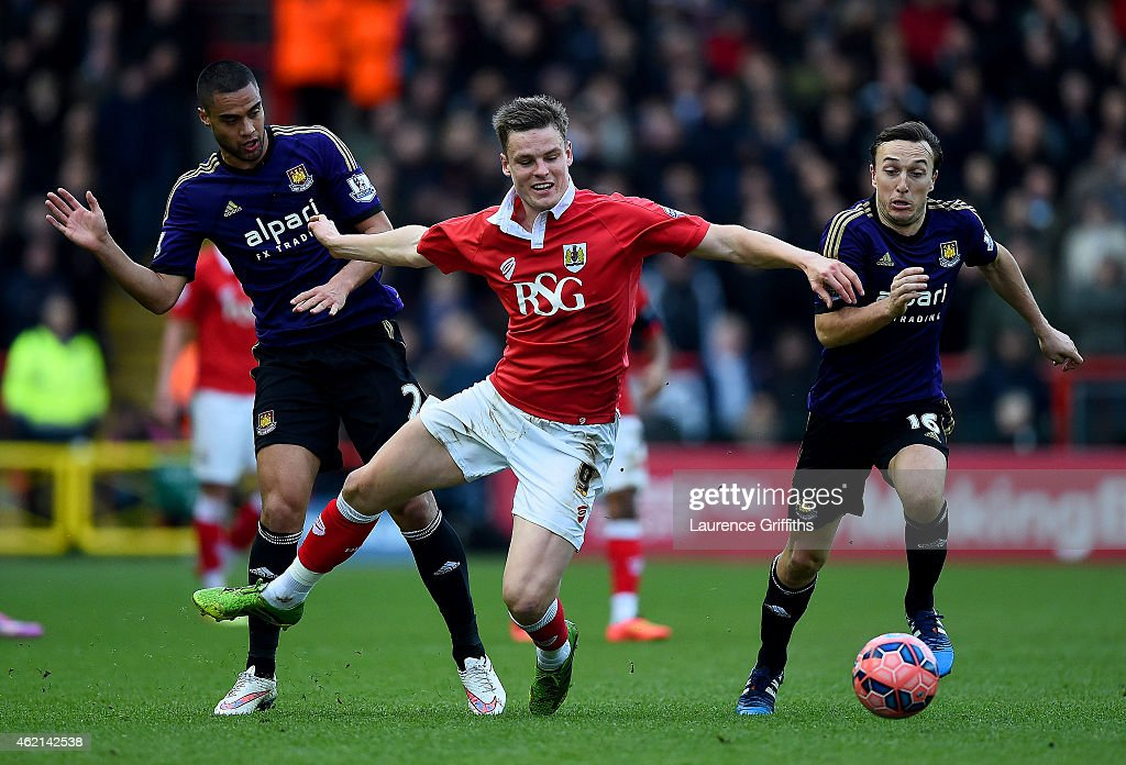 Matt Smith of Bristol City battles for the ball with Winston Reid and Mark Noble of West Ham during the FA Cup Fourth Round match between Bristol City and West Ham United at Ashton Gate on January 25, 2015 in Bristol, England.