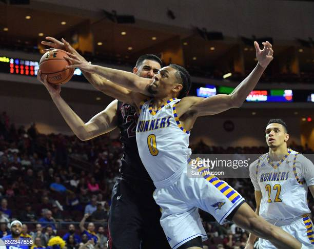 Matt Smith of the Cal State Bakersfield Roadrunners and Tanveer Bhullar of the New Mexico State Aggies fight for a rebound during the championship...