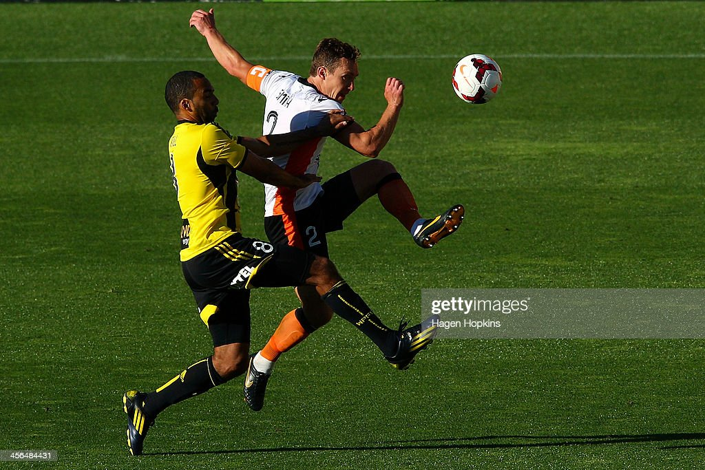 Matt Smith of the Roar volleys a high ball under pressure from Paul Ifill of the Phoenix during the round 10 A-League match between the Wellington Phoenix and Brisbane Roar at Westpac Stadium on December 14, 2013 in Wellington, New Zealand.