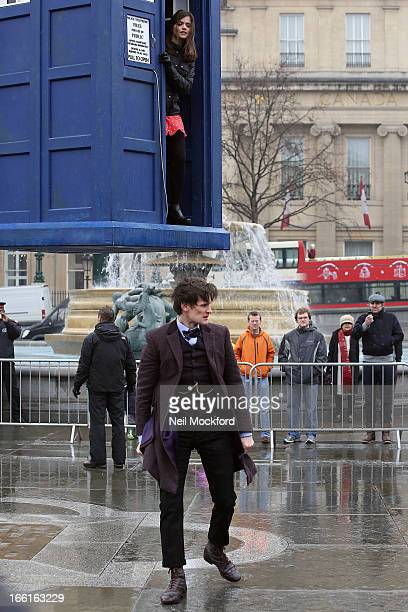Matt Smith stands beneath a suspended Tardis as Jenna-Louise Coleman stands inside the time machine during filming of Dr Who, in Trafalgar Square on...