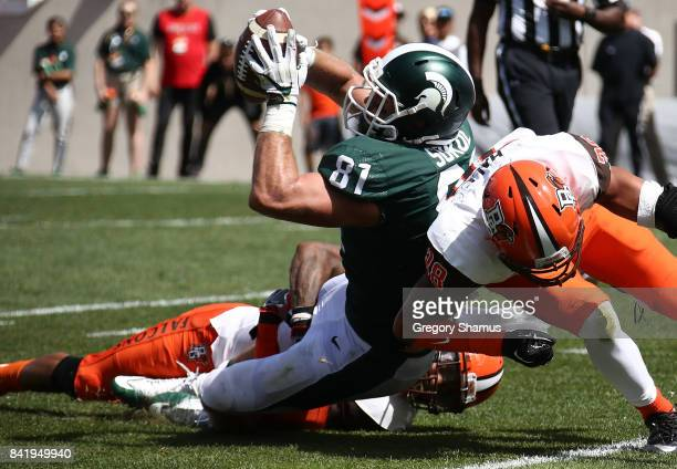 Matt Sokol of the Michigan State Spartans battles in for a second half touchdown past a hit by Ben Hale of the Bowling Green Falcons at Spartan...