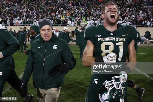 Matt Sokol of the Michigan State Spartans celebrates a 27-24 win over the Penn State Nittany Lions next to head coach Mark Dantonio at Spartan...
