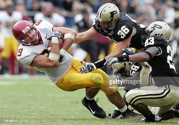 Matt Spaeth of the Minnesota Golden Gophers is tackled by Dan Bick Standford Keglar and Justin Scott of the Purdue Boilermakers during a Big Ten...