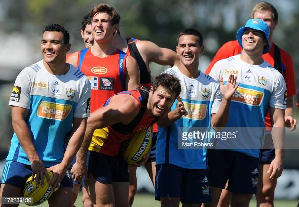 Matt Srama Marmin Barba and Aidan Sezer of the Titans share a laugh with David Swallow and Campbell Brown of the Suns after a Gold Coast Titans...