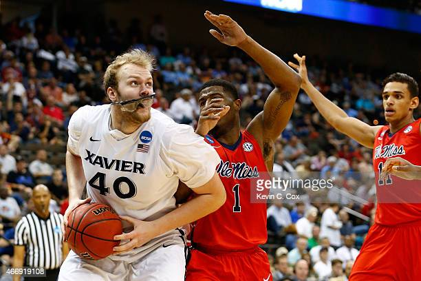 Matt Stainbrook of the Xavier Musketeers drives on Martavious Newby of the Mississippi Rebels in the second half during the second round of the 2015...