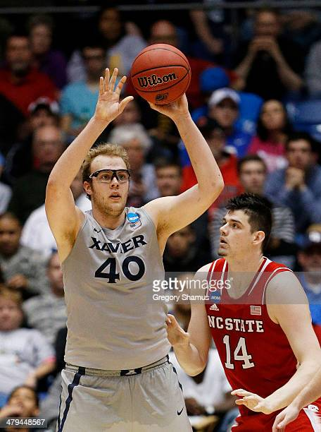 Matt Stainbrook of the Xavier Musketeers looks to pass against Jordan Vandenberg of the North Carolina State Wolfpack in the second half during the...