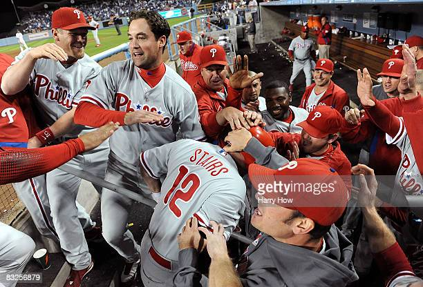 Matt Stairs of the Philadelphia Phillies celebrates with teammates after hitting a two-run pinch hit home run in the eighth inning off Jonathan...