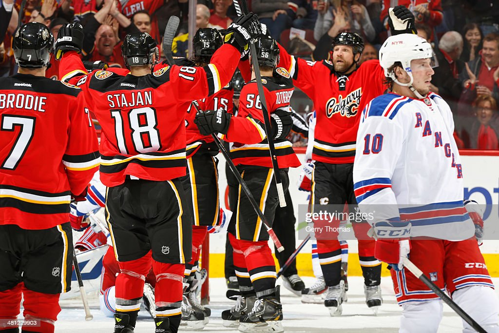 Matt Stajan #18 and Brian McGrattan #16 of the Calgary Flames celebrate a goal by Kevin Westgarth #15 against the New York Rangers at Scotiabank Saddledome on March 28, 2014 in Calgary, Alberta, Canada.