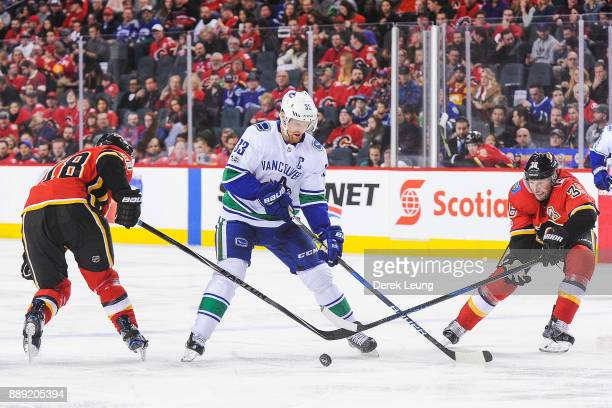 Matt Stajan and Troy Brouwer of the Calgary Flames check David Rittich of the Vancouver Canucks during an NHL game at Scotiabank Saddledome on...