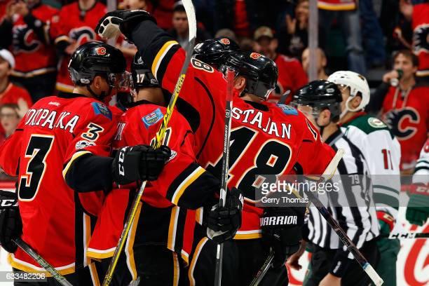 Matt Stajan Jyrki Jokipakka and teammates of the Calgary Flames celebrate a goal against the Minnesota Wild during an NHL game on February 1 2017 at...