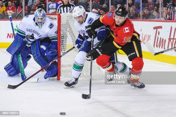 Matt Stajan of the Calgary Flames chases the puck against Sven Baertschi of the Vancouver Canucks during an NHL game at Scotiabank Saddledome on...