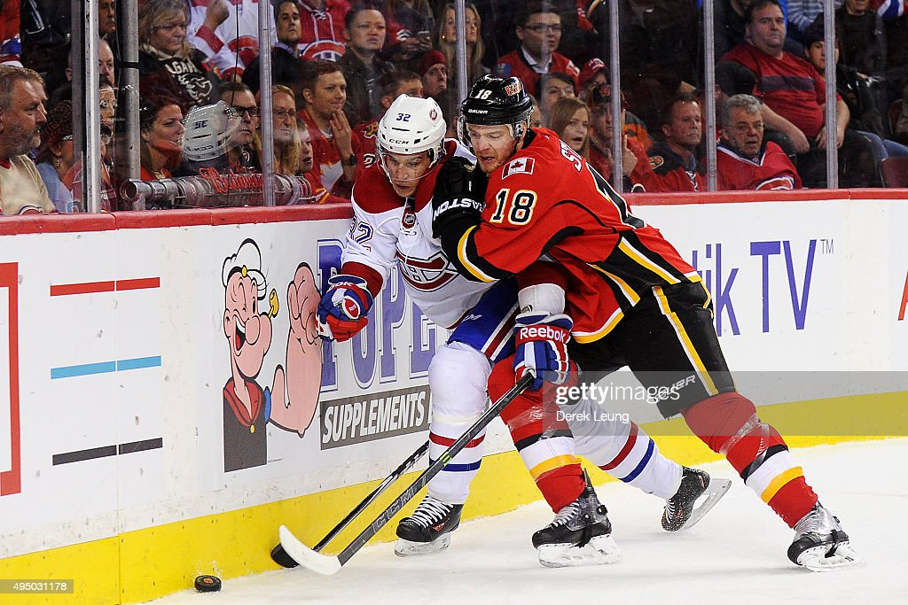 Matt Stajan #18 of the Calgary Flames checks Brian Flynn #32 of the Montreal Canadiens during an NHL game at Scotiabank Saddledome on October 30, 2015 in Calgary, Alberta, Canada.