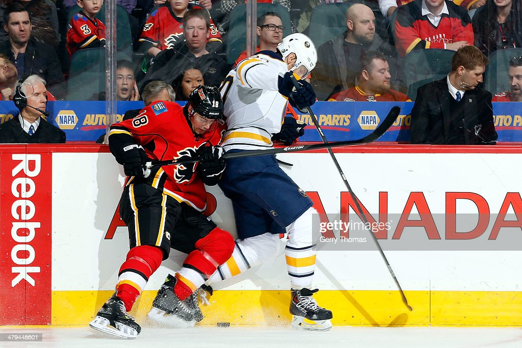 Matt Stajan #18 of the Calgary Flames digs for the puck along the boards against Henrik Tallinder #20 of the Buffalo Sabres at Scotiabank Saddledome on March 18, 2014 in Calgary, Alberta, Canada.