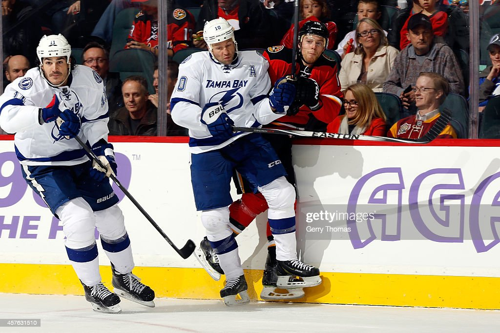 Matt Stajan #18 of the Calgary Flames is checked by Brenden Morrow #10 of the Tampa Bay Lightning at Scotiabank Saddledome on October 21, 2014 in Calgary, Alberta, Canada.